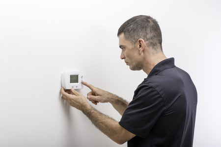 Hvac technician adjusting temperature on thermostat