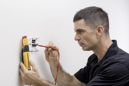 HVAC tech checking low voltage on a thermstat Standard-Bild