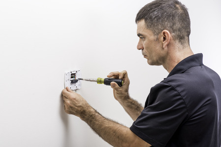 Hvac technician installing a digital thermostat