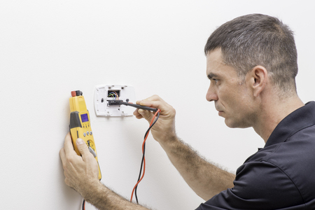 Trained HVAC technician checking troubleshooting a thermostat
