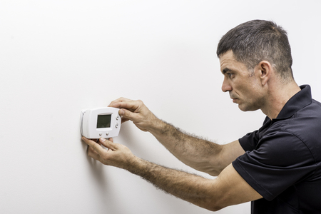 Hvac technician installing faceplate on a digital thermostat Stock Photo