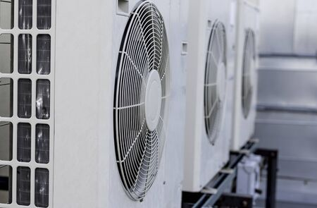 A row of mini-split air conditioner condensers on a rooftop of a building