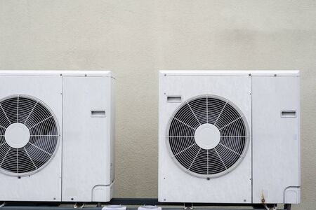 A couple mini-split air conditioner condensers outside, with beige wall in background Stock Photo