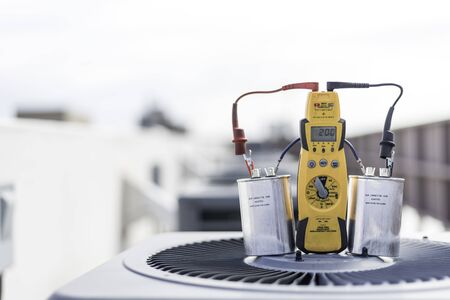 Multimeter and two run capacitors placed on a condenser, wired in series, being tested for microfarads Banque d'images - 132085958