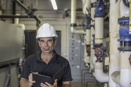 Hvac technician standing in a boiler room while writing on a tablet