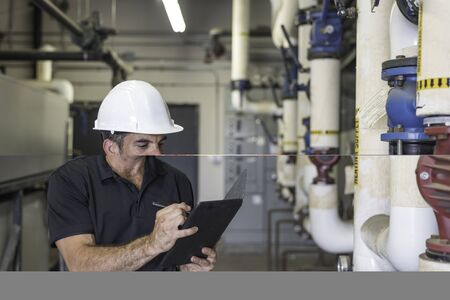 Hvac technician writing on a tablet, standing in a boiler room