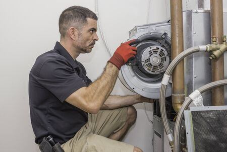 HVAC technician removing a furnace blower motor from a commercial heat pump. Repair man wearing a uniform and safety gloves.