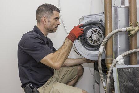 Technicien en CVC retirant un moteur de ventilateur de fournaise d'une thermopompe commerciale. Homme de réparation portant un uniforme et des gants de sécurité.