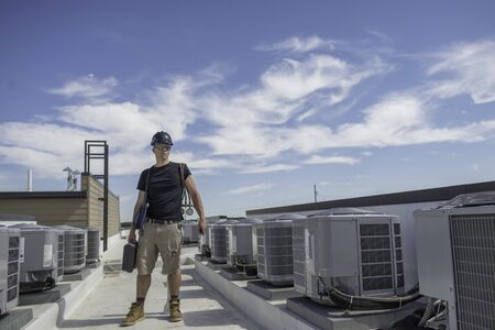 Hvac technician holding tools, standing next to a row of condensers on a roof. Stock Photo