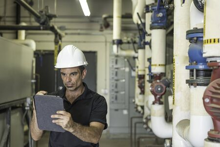 Hvac tech looking over his tablet, inside of a boiler room, shallow depth of field