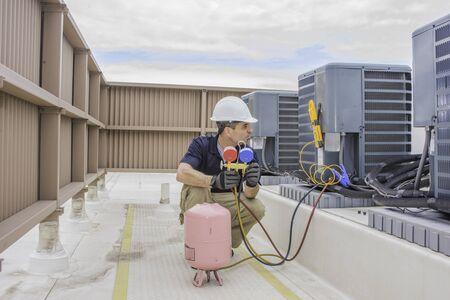 Técnico de servicio de HVAC cargando una unidad de condensación con refrigerante 410A