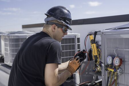 HVAC technician working on condensing unit electrical