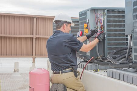 Technician checking for power on a rooftop condensing unit. Stock Photo