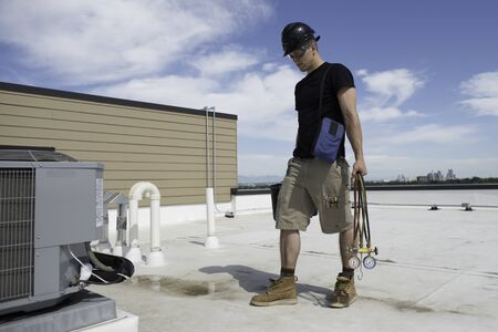 Hvac tech walking up on a rooftop condenser that has a frozen suction line Stock Photo