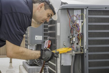 Professional hvac technician measuring amperage on an air conditioner unit Stock Photo