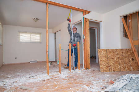 Carpenter measuring a room that has had the drywall and flooring demolished for a home renovation project.
