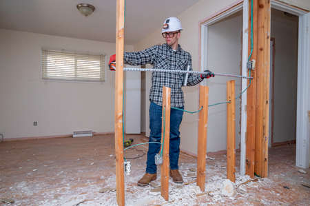 Carpenter measuring framing studs in a room where the drywall has been removed for a home improvement project Banque d'images