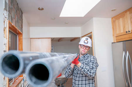 Construction worker inside unfinished home kitchen holding PVC pipe.