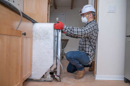 Contractor inside home kitchen removing dishwasher unit during remodeling project Banque d'images