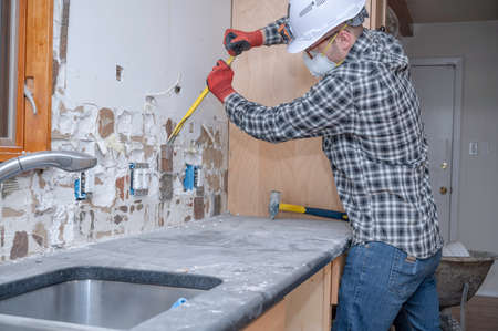 A renovation worker removing kitchen wall tile during a home improvement project. Banque d'images