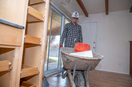 Contractor inside home with wheel barrel filled with buckets during home remodel project.