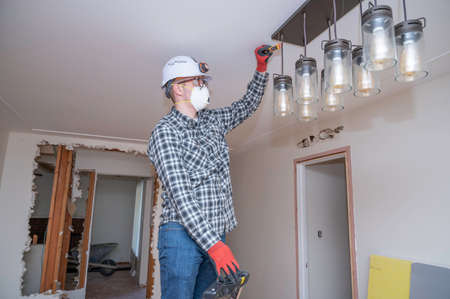 Electrician testing electrical current on a lighting fixture during a home remodel. Banque d'images