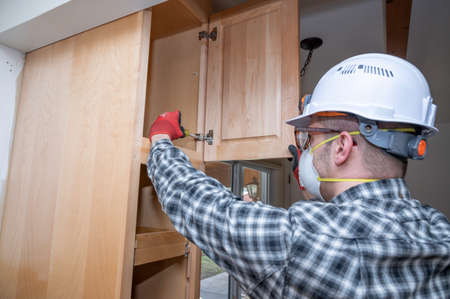 Contractor tightening cabinet doors during a home kitchen remodeling project.