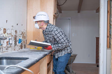 Electrician inspecting electrical outlet inside kitchen of a home remodel.