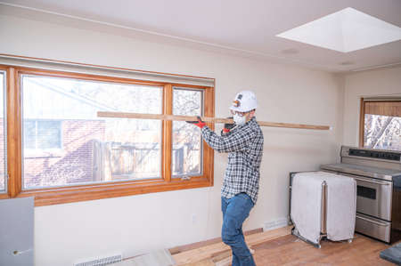 Contractor carrying a framing stud inside of a dining room during a home remodel.
