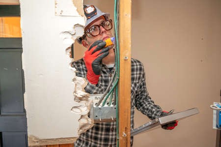 Electrician inspecting electrical wiring between framing studs where the drywall is removed for home renovation project