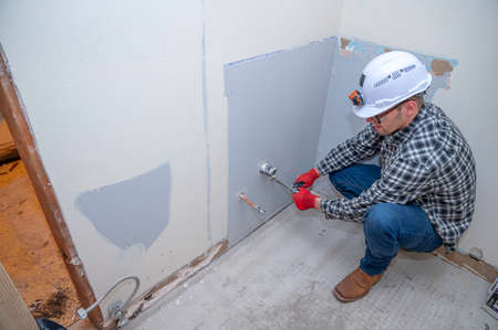 Plumber installing new pipes in bathroom during home remodeling project