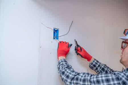 Electrician cutting wires in walls of home remodel project