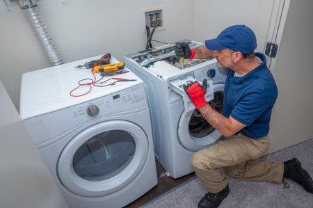 Appliance technician working under a kitchen sink installing a dishwasher