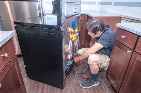 Appliance technician or handyman repairing or troubleshooting an electric range inside of a residential home