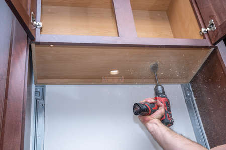 Drilling a hole underneath a hanging cabinet for a microwave installation or a home remodel