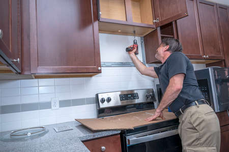 An appliance technician or diy repairman drilling a hole through a cabinet for a microwave installation or kitchen remodel