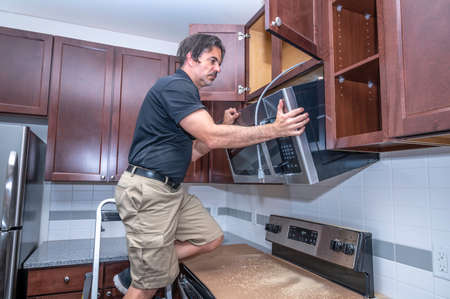 Appliance technician on a step ladder installing a over the range microwave to a cabinet