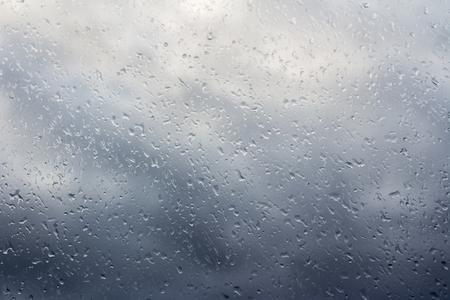 Stormachtige wolken door het natte raam