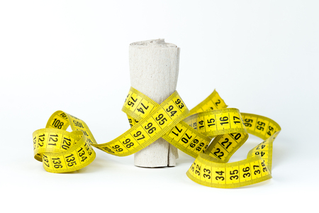 Measuring tape wrapped around toilet paper on a white background