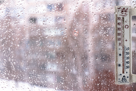 A thermometer on windows covered with raindrops, as a symbol of bad weather Stock Photo