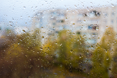 rain outside the window, raindrops on the windowpane on a cloudy day