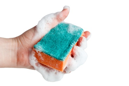 Hand grasps sponge for washing dishes on white background