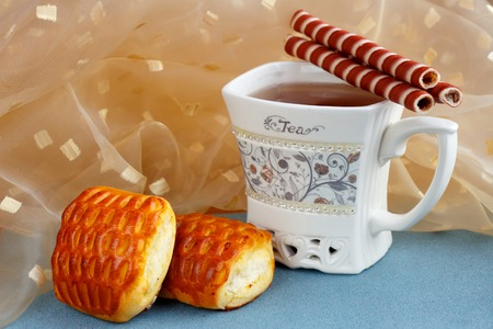 image of cup with tea and biscuits closeup