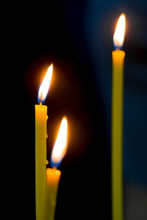 candles burn with a beautiful calm bright flame against a dark background.