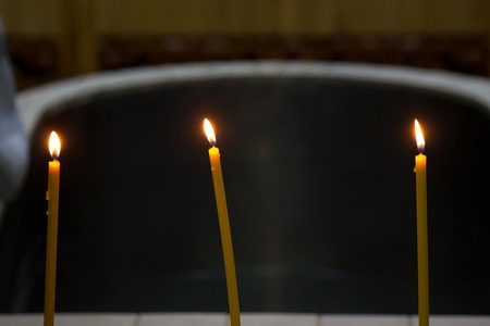 Three candles on the edge of the font in the Russian Orthodox Church