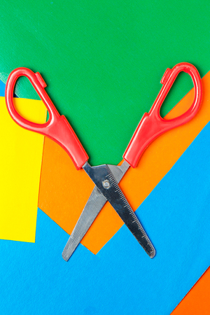 Scissors lie on multicolor paper. Green, Orange, Yellow, Blue