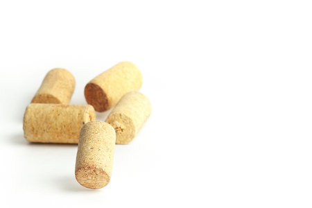 Corks stacked at random heights against white background.