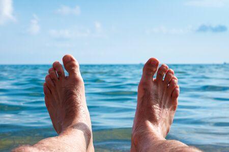 I enjoy the sea. A man lies on the beach opposite the sea