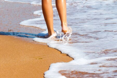 Feet girl barefoot walking by the sea. The girl touches the foot of the water. Stock Photo