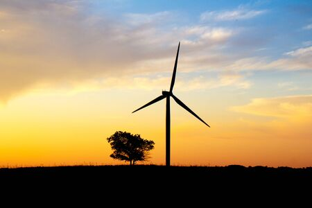 Silhouette of wind farm on sunset background